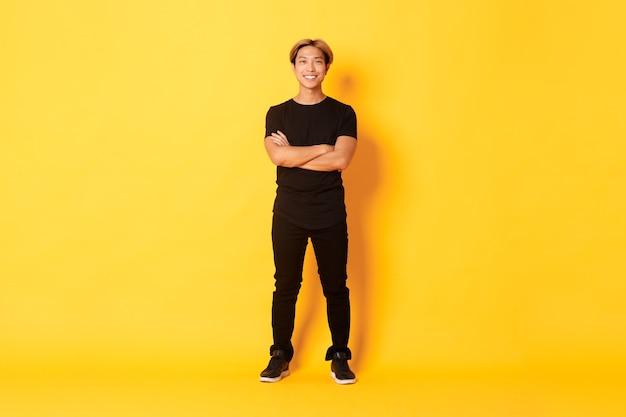 미소 자신감 아시아 blong 남자의 전체 길이, 노란색 벽에 팔 가슴을 교차.