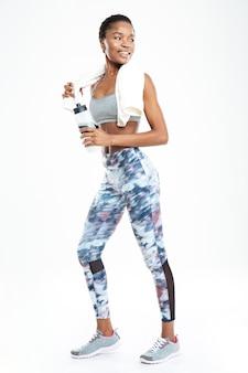 Полная длина улыбающейся милой молодой афро-американской спортсменки, стоящей и держащей бутылку воды