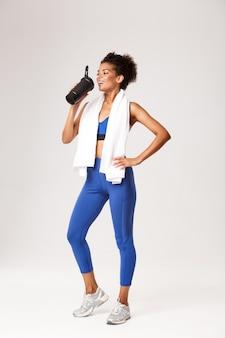 青いスポーツ服を着た笑顔の女性アスリートの全長、ボトルからタンパク質または水を飲む