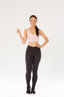 웃는 예쁜 아시아 피트니스 소녀의 전체 길이, 왼쪽 손가락을 가리키는 활성 착용 여성 운동 선수, 훈련 장비를 보여주는 체육관 코치
