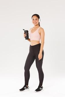 スリムで幸せなフィットネスの女の子の笑顔の全長、ヘッドフォンでジムでアジアの女性アスリートトレーニング、トレーニング中に音楽を聴く、エクササイズの合間にボトルから水を飲む、白い背景。