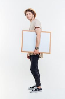 白い背景の上に空白のホワイトボードを歩いて保持している笑顔の若い男の全長