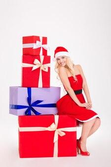 Полная длина улыбающейся молодой женщины в красном костюме санта-клауса и шляпе, сидящей на подарочных коробках на белом фоне