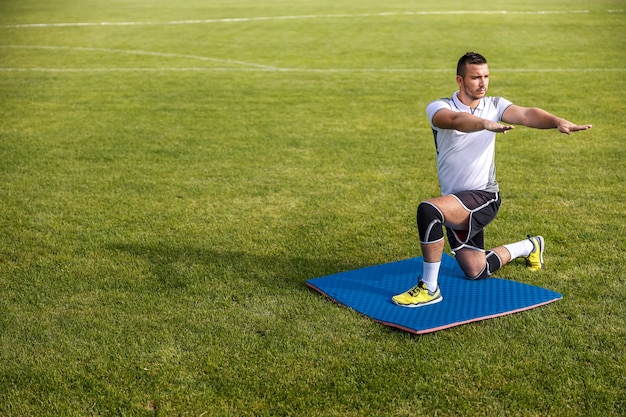 ひざまずいてフィールドでウォームアップ運動をしているサッカー選手の全身像。