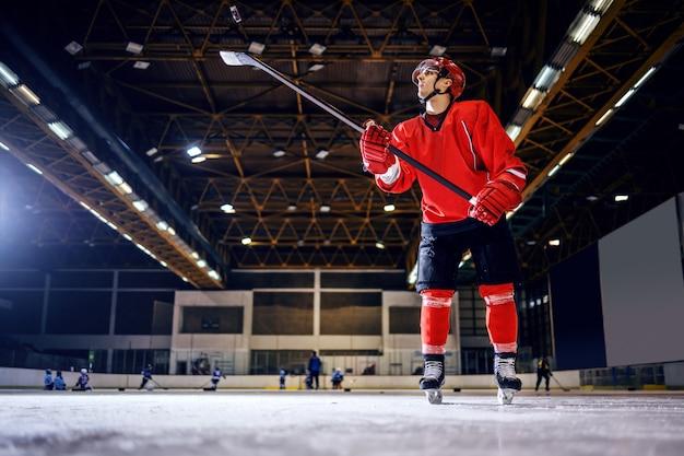 制服を着た強いホッケー選手の全長。ヘルメットを棒で振り、シュートをゴールに向けて準備する。