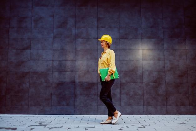Полная длина успешного кавказского белокурого старшего женского архитектора со шлемом на голове и папкой с документами под подмышкой, проходящей мимо серой стены и идущей к строительной площадке.
