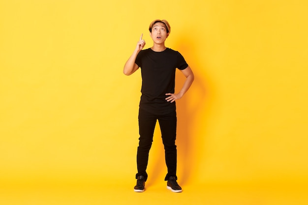 思慮深く、興味をそそられる魅力的なブロンドアジア人男性の指を上げ、上向きにして面白がって見える黄色の壁