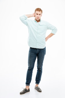 Вдумчивый молодой человек в полный рост стоит и думает над белой стеной