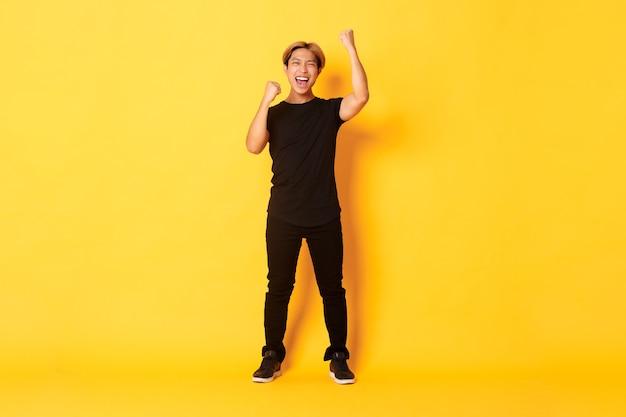 Торжествующий красивый азиатский мужчина в полный рост со светлыми волосами, поднимает руки вверх в знак празднования, говорит «да», стоя у желтой стены.