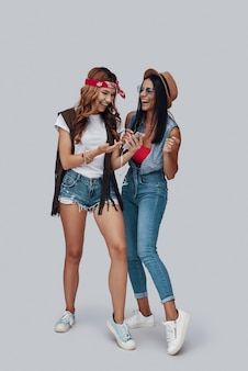 회색 배경에 서있는 동안 음악을 듣고 웃고 두 매력적인 세련된 젊은 여성의 전체 길이