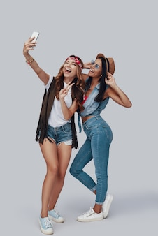 회색 배경에 서있는 동안 셀카를 복용하고 웃는 두 매력적인 세련된 젊은 여성의 전체 길이