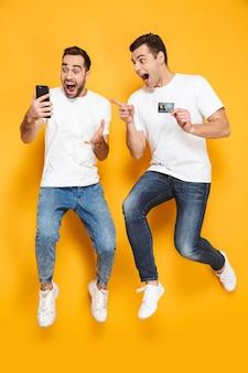 Два веселых взволнованных друга-мужчины в пустых футболках прыгают изолированно через желтую стену, глядя на мобильный телефон, празднуя успех