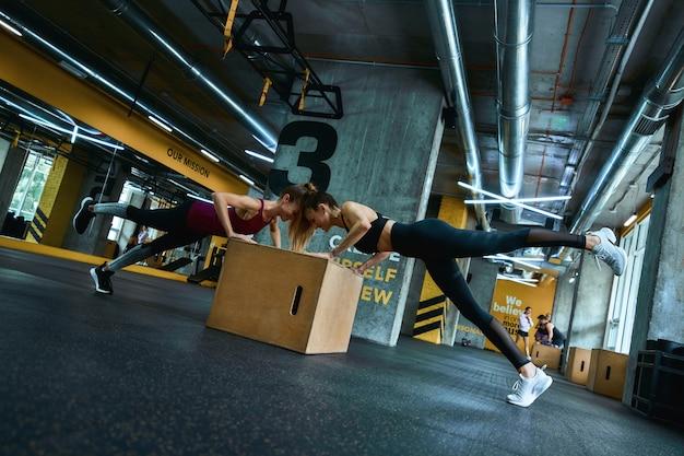 ジムで木製のクロスフィットジャンプボックスで腕立て伏せをし、一緒に運動しているスポーツウェアの2人の若い運動女性の全長。陽気な人々、健康的なライフスタイルとトレーニングの概念
