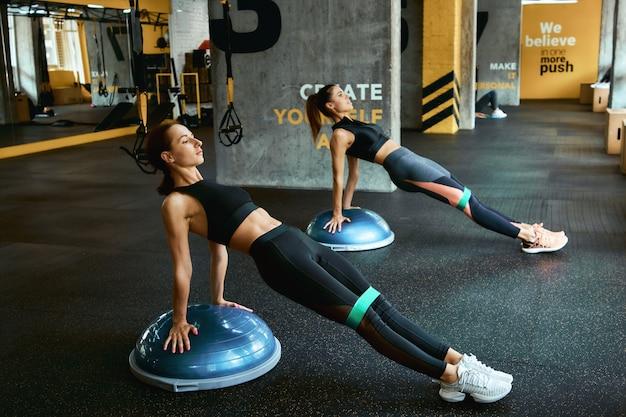 特別なスポーツ用品を使用して、クロスフィットジムでレジスタンスフィットネスバンドで運動しているスポーツウェアの2人の若いアスリート女性の全長。トレーニング、トレーニング、ウェルネス、ボディケア