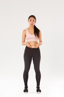 フィットネス服を着た、動揺して暗いアジアの女の子の全身、腹に脂肪を示し、体に不平を言い、眉をひそめ、失望しているように見え、トレーニングを開始し、体重を減らそうとしている、白い背景。