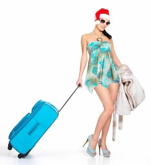 Полная длина женщины в шляпе санта-клауса, стоящей с дорожным чемоданом