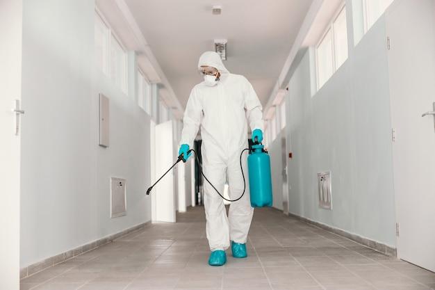 無菌の制服を着た完全な長さの労働者。消毒剤が付いた噴霧器を保持し、学校の廊下に噴霧するフェイスマスク。