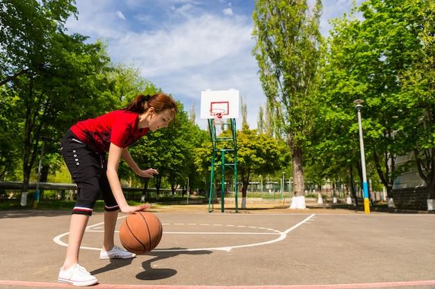 バックボードとバスケットを背景に緑豊かな緑豊かな公園の中庭でバスケットボールをドリブル若い運動女性の全長