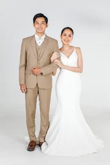 若い魅力的なアジアのカップル、花嫁と花婿、白いウェディングドレスを着ている女性の全長。ベージュのスーツを着て、腕を組んで一緒に立っている男。結婚式前の写真撮影のコンセプト。