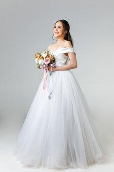 花の花束を持って幸せそうに見える白いウェディングドレスを着て、すぐに花嫁になる若い魅力的なアジアの女性の全長。結婚式前の写真撮影のコンセプト。