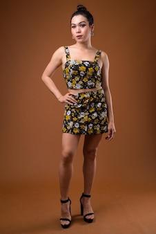 Полная длина молодой красивой азиатской трансгендерной женщины, стоящей