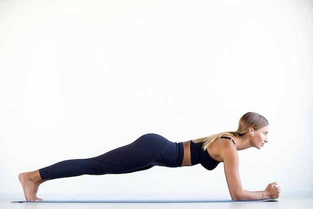 판자를 하 고 체육관에서 그녀의 핵심 근육을 작동하는 운동복에 젊은 아름 다운 여자의 전체 길이입니다.