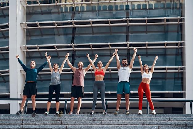 屋外に立っている間、腕を伸ばして笑顔を保つスポーツウェアの若者の全身
