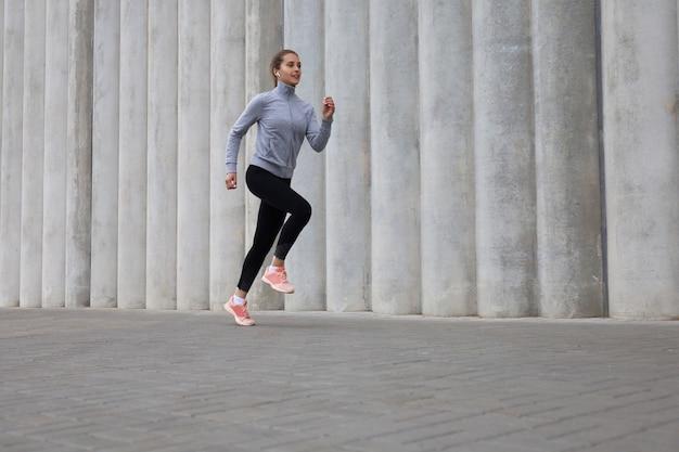 야외 운동을 하는 동안 조깅을 하는 스포티한 젊은 여성의 전체 길이입니다.