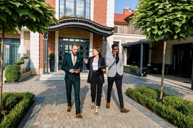 Полная длина трех молодых улыбающихся многорасовых бизнесменов, обсуждающих встречу во время прогулки на свежем воздухе перед современным зданием, офисом, рестораном или гостиницей