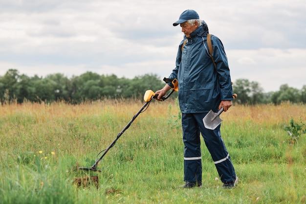 ジャケットと帽子をかぶった貨幣学者の完全な長さの屋外ポートレート、手にシャベルと金属探知機を持ち、牧草地で金や歴史的遺物を探している。