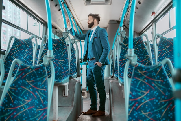 Full length of pensive caucasian businessman in blue suit standing in public transportation and going to work.