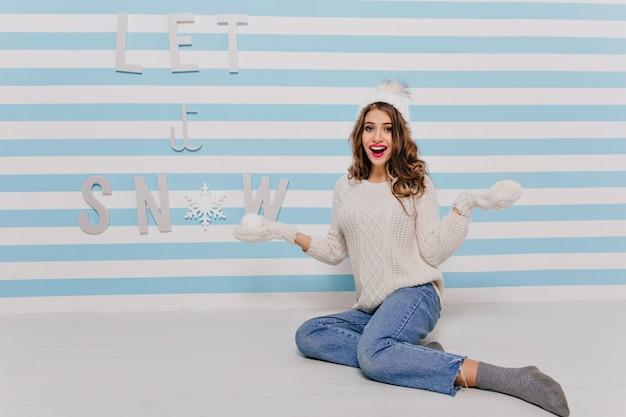 따뜻한 겨울 옷을 입고 눈덩이와 함께 포즈를 취하는 바닥에 놀라움에 앉아 젊은 러시아 여자의 흰색 비문 벽에 전체 길이 사진