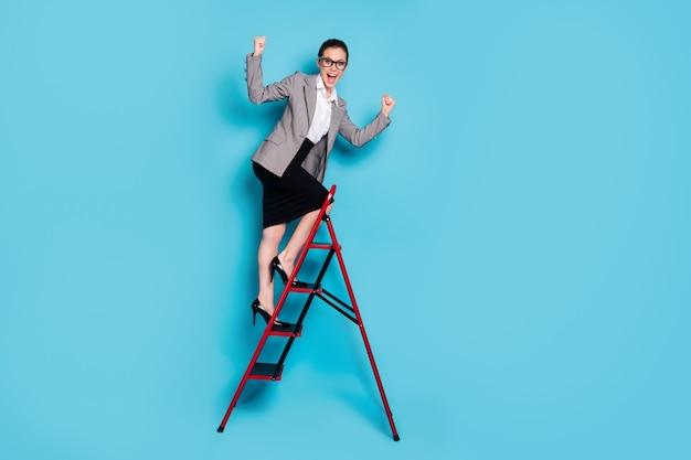 전체 길이 사진 에이전트 여자 등반 경력 사다리 상승 주먹 비명 착용 재킷 치마 고립 된 파란색 배경