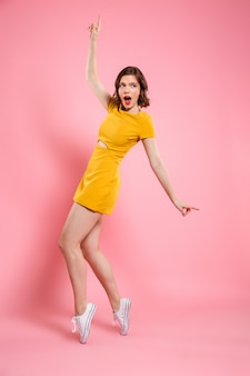 Full length photo of amazed pretty brunette woman standing in fashion pose, pointing with finger, looking aside