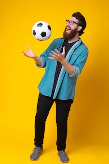 Full length photo of amazed young man with beard holding soccer ball over yellow