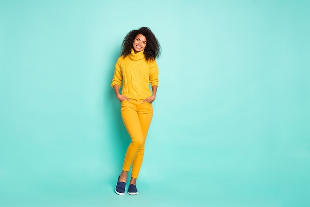 Full length photo of amazing dark skin lady holding hands in pockets wear yellow knitted stylish pullover and trousers isolated blue teal color wall