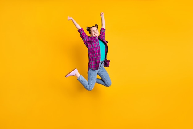 Full length photo of attractive crazy teen lady jump high up air flight ecstatic champion marathon sports competition wear casual plaid shirt shoes jeans isolated yellow color background