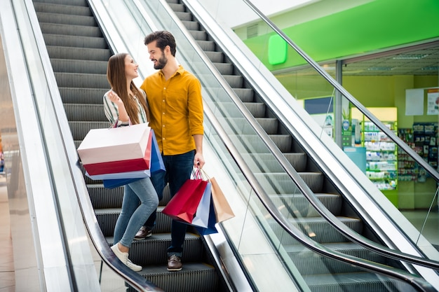 Full length photo of  attractive lady handsome guy couple spend free time carry many bags moving up escalator shopping center hug look eyes wear casual jeans shirt outfit indoors