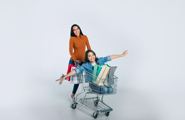 Full-length photo of attractive woman in casual clothes, who is pushing a shopping cart with her daughter, who is pointing forward, and three shopping bags in it.