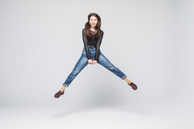 Foto integrale della donna attraente che salta in aria con le braccia tese. muro bianco.