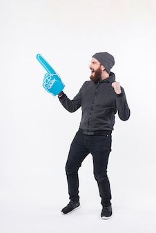 Full length photo of bearded man celebrating and pointing with fan glove