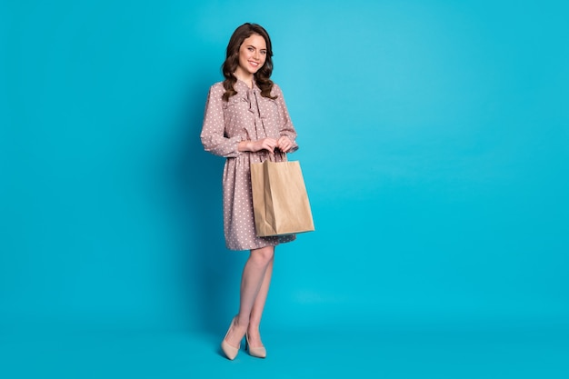 Full length photo of beautiful attractive lady hold paper bag buy food delivery restaurant takeaway service wear dotted short dress stilettos isolated blue color background
