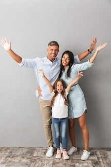 Full length photo of beautiful caucasian family woman and man with little girl smiling and hugging together, isolated over gray