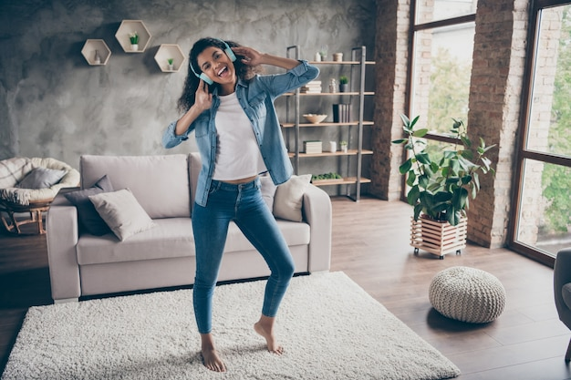 Full length photo of beautiful dark skin wavy lady wear modern earflaps singing listening cool songs standing floor near couch casual denim outfit living room indoors