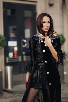 Foto a figura intera di bella donna elegante che cammina per strada mentre indossa una sciarpa di seta sulla testa. concetto di bellezza e moda