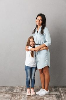Full length photo of beautiful woman with little girl smiling and hugging together, isolated over gray