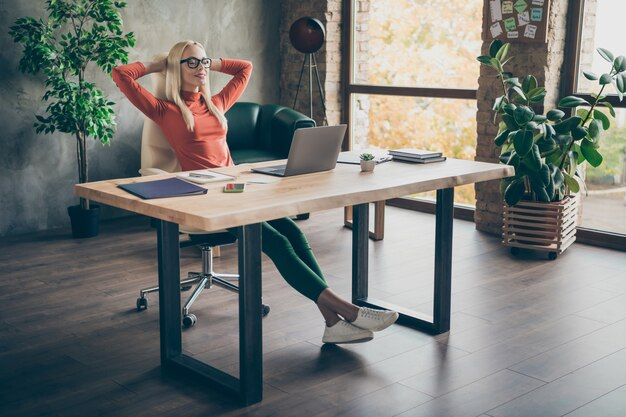 Full length photo of calm positive peaceful woman company owner attorney finish start-up work sit table relax close eyes stretch hands in office loft red turtleneck