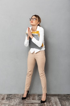 Full length photo of caucasian businesswoman wearing glasses holding paper folders in the office, isolated