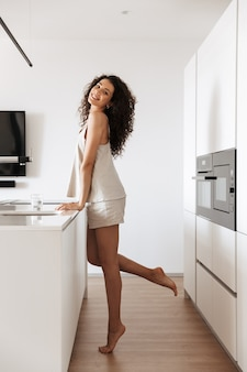 Full length photo of caucasian curly woman with long dark hair wearing silk leisure clothing smiling, and standing in kitchen near cooking place