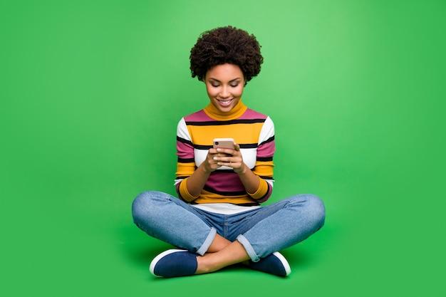 Фото в полный рост жизнерадостная афроамериканская девушка сидит, сложив ноги, пользуется смартфоном, читайте новости в соцсетях, комментарий следуйте за репостом, наденьте джинсовые джинсы, яркую одежду
